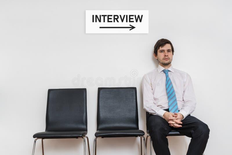 Ein Mann sitzt auf Stuhl im Warteraum und in Warteinterview lizenzfreie stockfotos