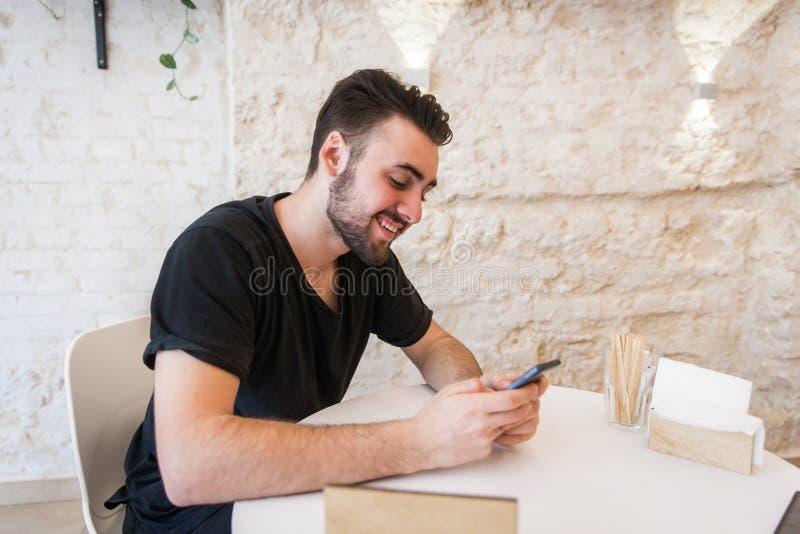 Ein Mann sitzt in einem Café und hält ein Telefon in seiner Hand, das Lächeln nett lizenzfreies stockbild