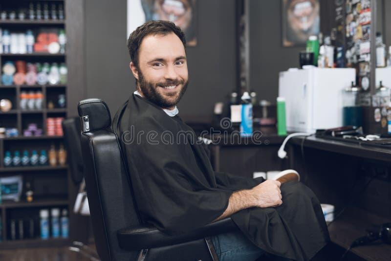 Ein Mann sitzt in einem Friseur ` s Stuhl in einem Mann ` s Friseursalon, wohin er kam, sein Haar zu schneiden lizenzfreies stockfoto