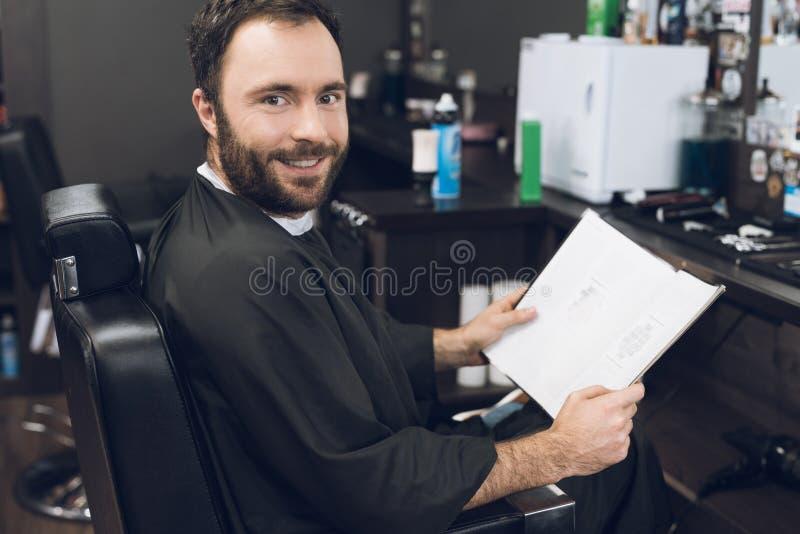 Ein Mann sitzt in einem Friseur ` s Stuhl in einem Mann ` s Friseursalon, wohin er kam, sein Haar zu schneiden stockfoto