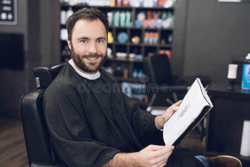Ein Mann sitzt in einem Friseur ` s Stuhl in einem Mann ` s Friseursalon, wohin er kam, sein Haar zu schneiden lizenzfreies stockbild