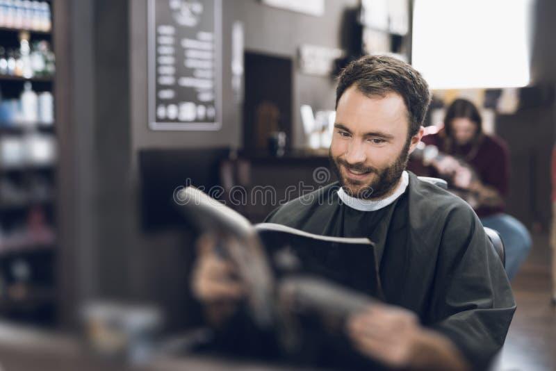 Ein Mann sitzt in einem Friseur ` s Stuhl in einem Mann ` s Friseursalon, wohin er kam, sein Haar zu schneiden stockbild