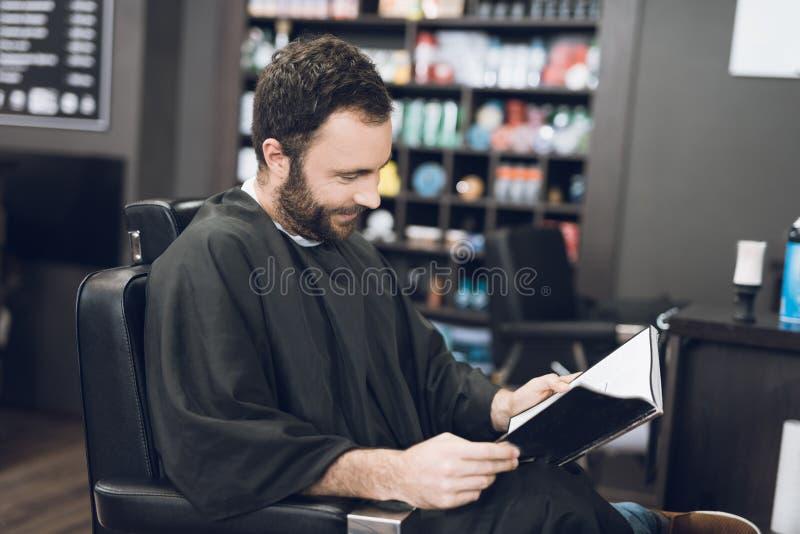 Ein Mann sitzt in einem Friseur ` s Stuhl in einem Mann ` s Friseursalon, wohin er kam, sein Haar zu schneiden lizenzfreie stockfotos