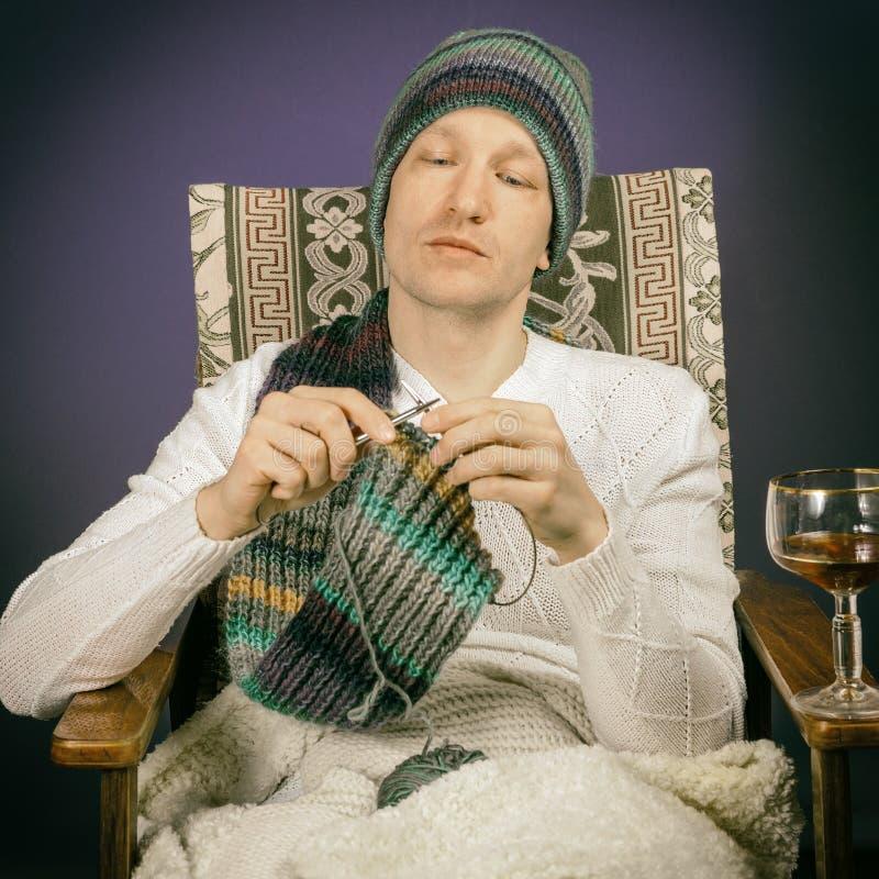 Ein Mann sitzt in einem Stuhl mit Wein in einer gestrickten Strickjacke und in einer Kappe und bindet den Schal mit den Nadeln se stockfotos