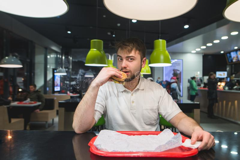 Ein Mann sitzt an einem Tisch in einem schnellen wickelnden Restaurant, isst köstliches Lebensmittel und betrachtet die Kamera stockfoto