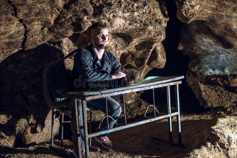 Ein Mann sitzt an einer Schulbank in einer dunklen Höhle Mist und Verwirrung auf dem Gesicht Lustige schlechte Bedingungen für St stockfoto