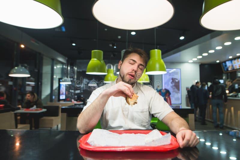 Ein Mann sitzt im bisro mit Burger in seinen Händen und genießt den Geschmack des köstlichen Lebensmittels Ein Mann mag köstliche stockbild