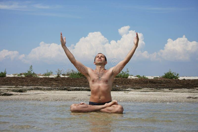 Ein Mann sitzt an Land Meer in der Haltung von Lotos stockbild
