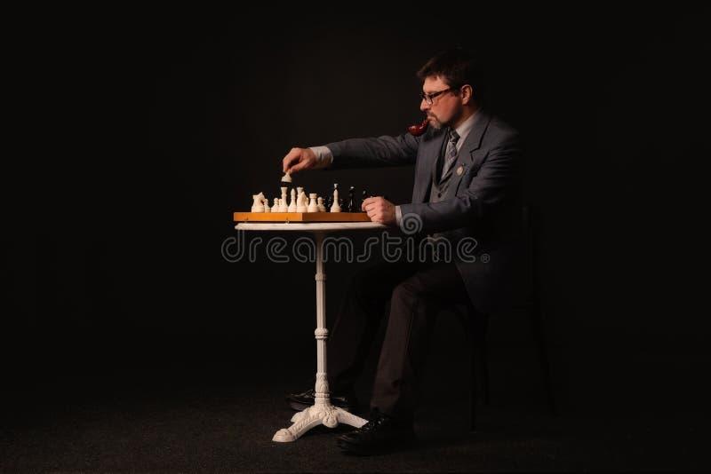 Ein Mann spielt Schach und raucht ein Rohr auf einem dunklen Hintergrund stockfoto