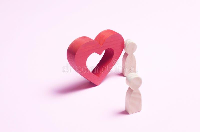 Ein Mann steht nahe dem Herzen und bekennt Liebe auf einem rosa backgro stockfotos