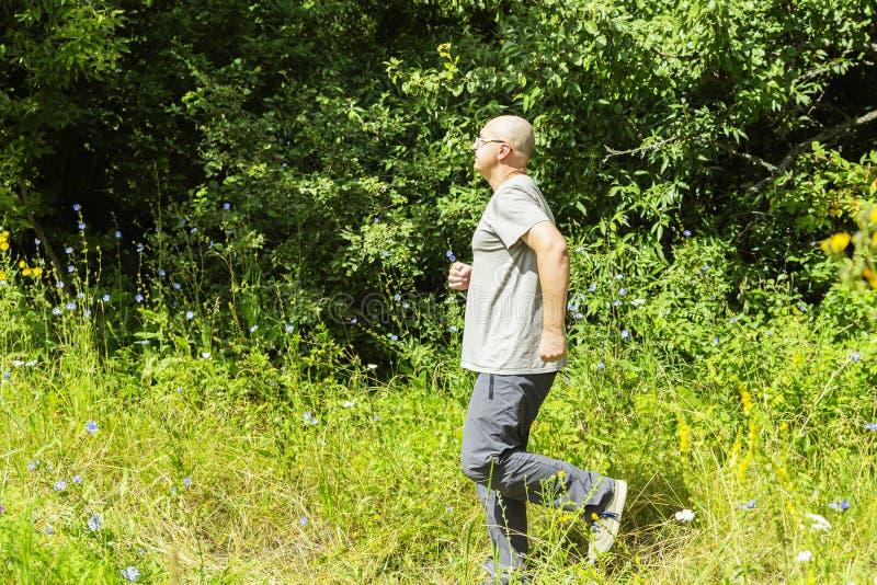 Ein Mann strebt herein Sport an Überladener Mann, der in Natur läuft stockbilder
