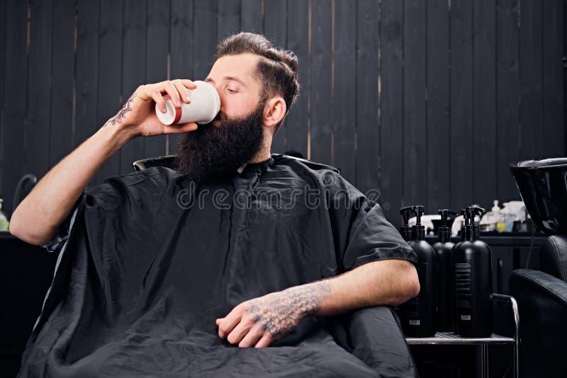 Ein Mann trinkt Kaffee in einem Friseur ` s Salon lizenzfreies stockbild