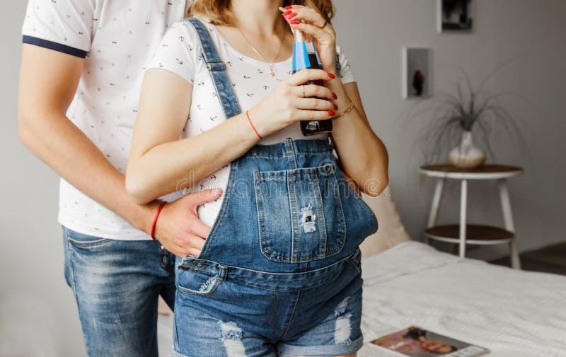 Ein Mann umarmt eine schwangere Frau durch den Magen lizenzfreie stockfotografie