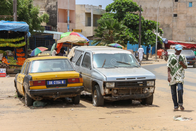 Ein Mann und defekten Autos in Dakar in Senegal lizenzfreie stockfotografie