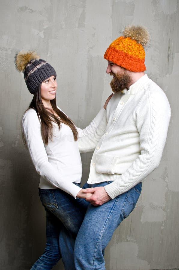 Ein Mann und eine Frau in einer Strickmütze mit Pelz Pom-poms betrachten einander und lächeln lizenzfreies stockbild