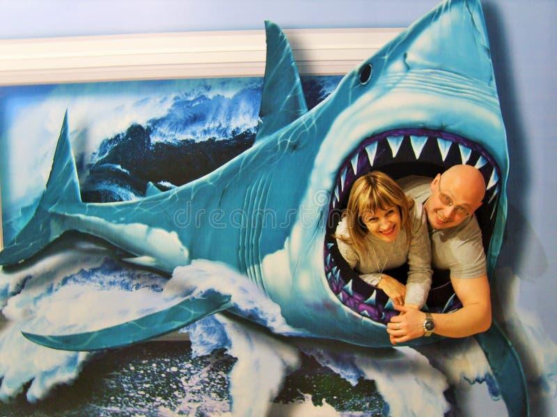 Ein Mann und eine Frau gezeichnet in die Kiefer eines Haifischs stockbild