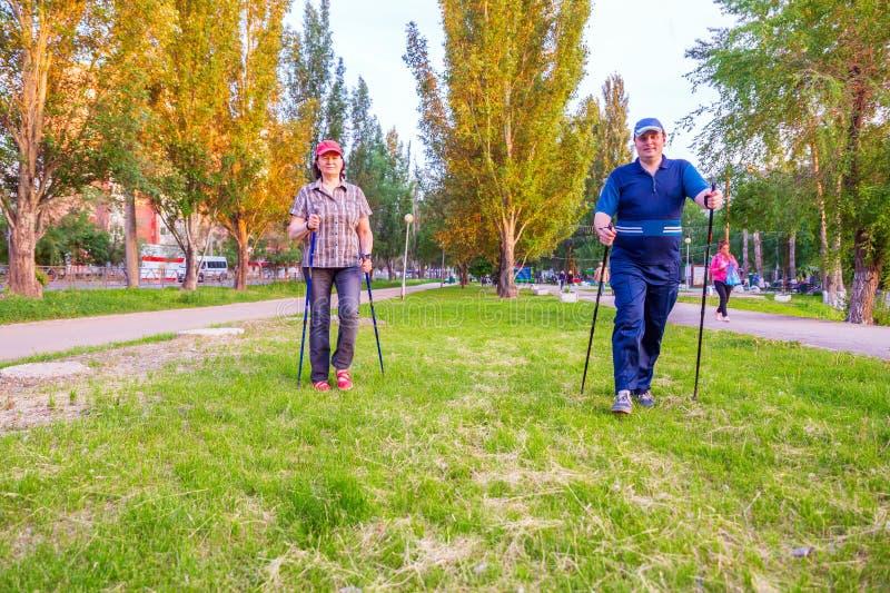 Ein Mann und eine Frau nehmen an dem nordischen Gehen teil lizenzfreie stockfotos