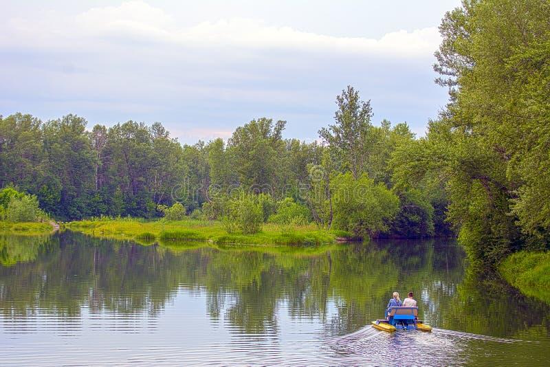 Ein Mann und eine Frauenfahrt auf ein Katamaran auf dem See, gegen den Hintergrund des Waldes lizenzfreie stockfotos