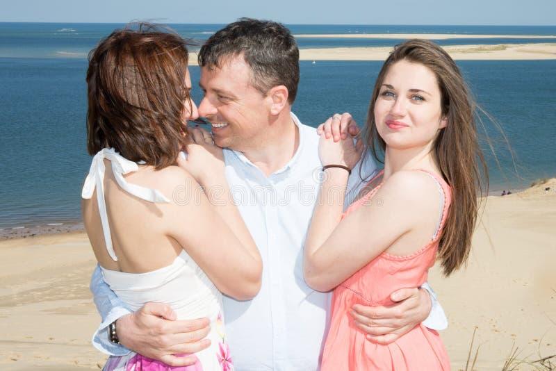 Ein Mann und Mädchen zwei fühlen sich auf dem Strand frei, der Kuss in der Liebe schaut stockbild