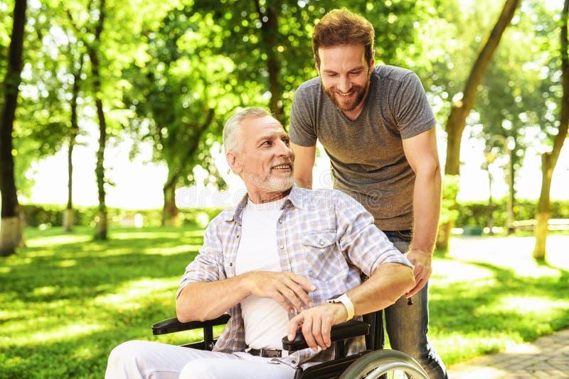 Ein Mann und sein älterer Vater gehen in den Park Ein Mann trägt seinen Vater in einem Rollstuhl lizenzfreie stockbilder