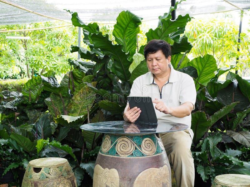 Ein Mann und seine Tablette sitzen im Garten lizenzfreie stockbilder