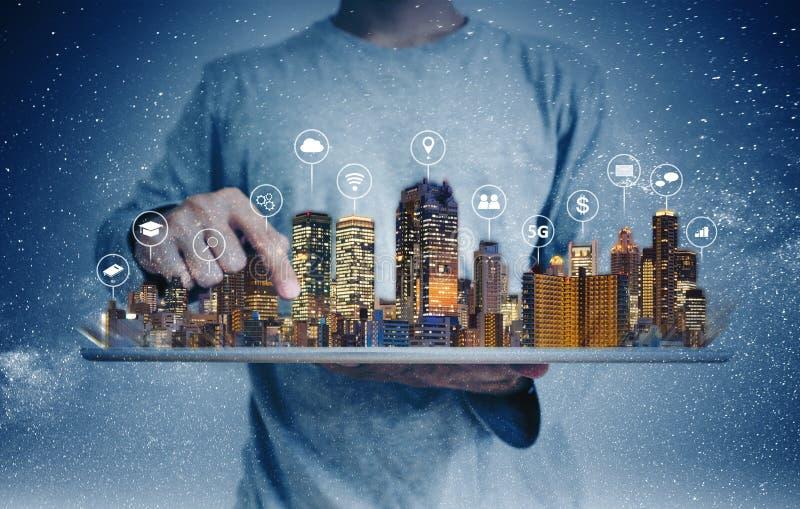 Ein Mann unter Verwendung der digitalen Tablette mit Gebäudehologramm- und -internet-Medienikonen Intelligenter Stadt-, 5g-, Inte