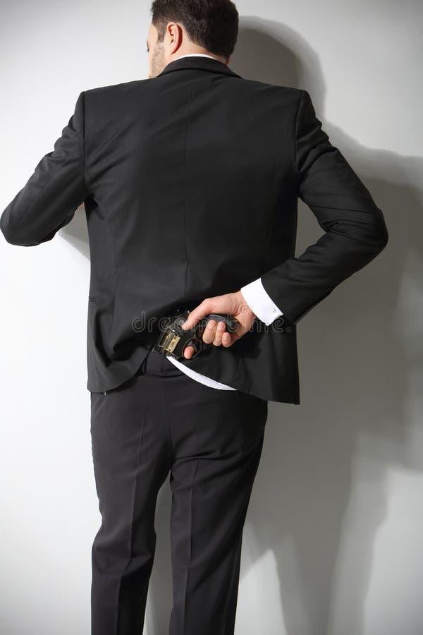 Ein Mann verbirgt eine Feuerwaffe in der Rückseite stockbild