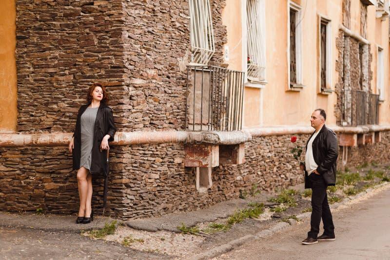 Ein Mann von mittlerem Alter mit einer roten Rose in seinen H?nden n?hert sich einer rothaarigen Frau auf einer Stadtstra?e stockfotos