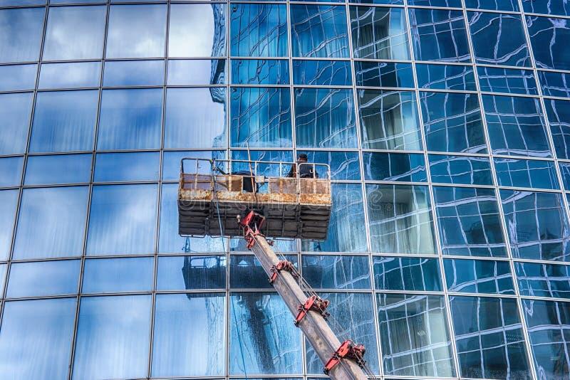 Ein Mann wäscht Fenster eines Wolkenkratzers lizenzfreies stockfoto