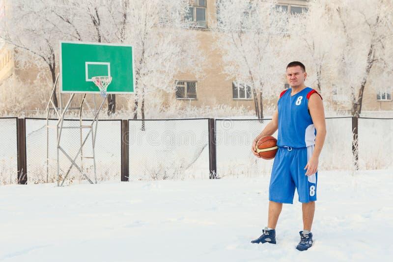 Ein Mannbasketball-spieler in der blauen Sportuniform steht auf einem Basketballplatz und hält einen Basketball in seinen Händen  lizenzfreies stockbild