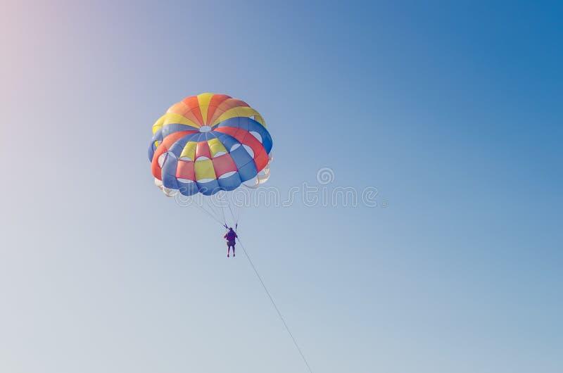 Ein Mannfliegen auf einem Fallschirm über dem Meer mit einem Boot lizenzfreie stockbilder