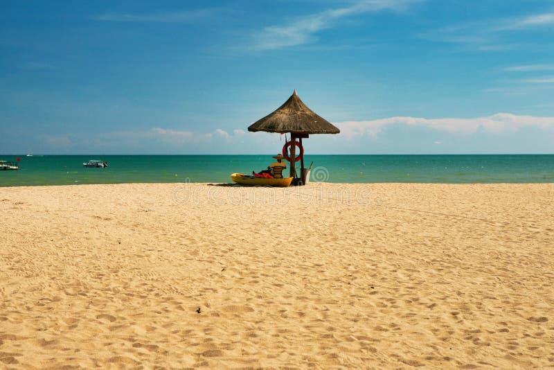 Ein Mannleibwächter, sitzend unter einem Regenschirm von Palmblättern auf einem einsamen Strand von Hainan-Insel lizenzfreies stockbild