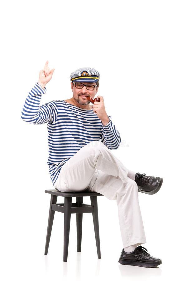 Ein Mannseemann in einer Kappe mit einer Pfeife vor einem weißen Ba stockfotografie