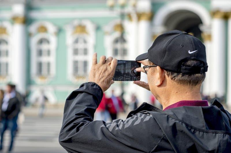Ein Manntourist von asiatischen Auftrittphotographien auf einem Smartphone das Einsiedlereigebäude auf dem Palastquadrat von St P lizenzfreie stockfotos