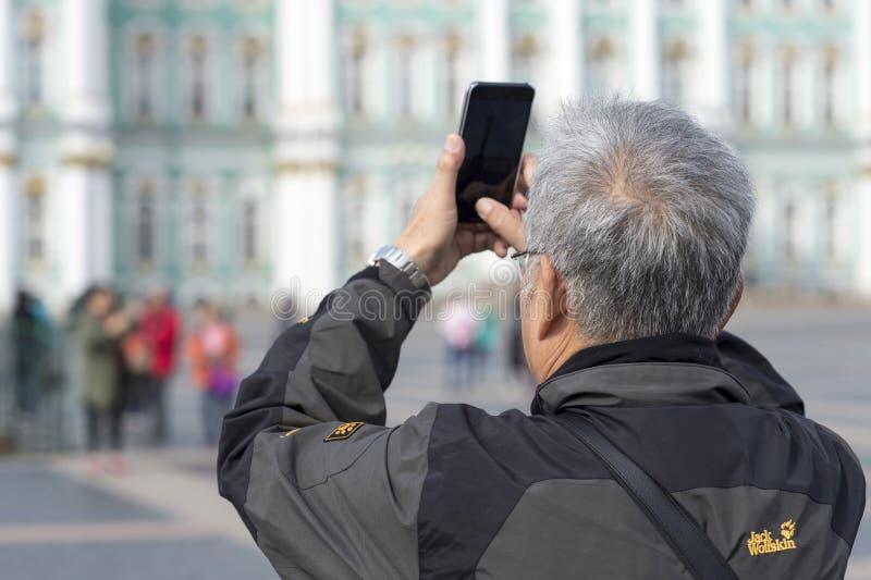Ein Manntourist von asiatischen Auftrittphotographien auf einem Smartphone das Einsiedlereigebäude auf dem Palastquadrat von St P stockfoto