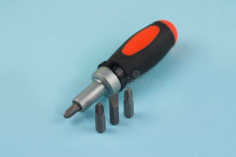 Ein manueller Schraubenzieher mit Gummigriff der schwarzen und orange Farbe nahe drei Bits für Schraubenzieher lizenzfreie stockfotografie