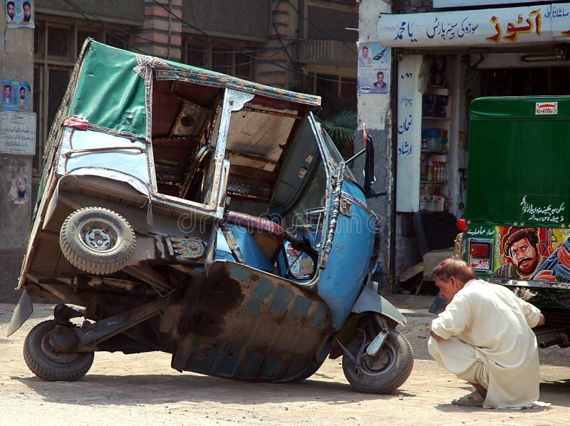 Ein Mechaniker behebt ein Problem mit seiner Rickshaw in Peshawar, Pakistan lizenzfreies stockfoto