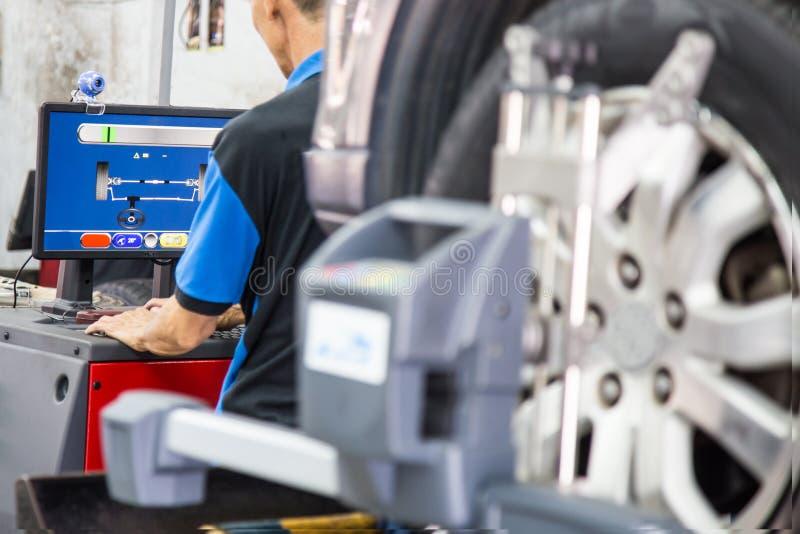 Ein Mechaniker, der den Computer benutzt, um den Radausrichtungsprozeß festzusetzen liest stockfotografie