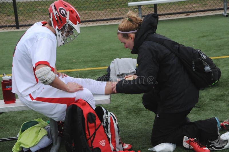 Ein Mediziner arbeitet an einem verletzten Spieler lizenzfreie stockfotografie
