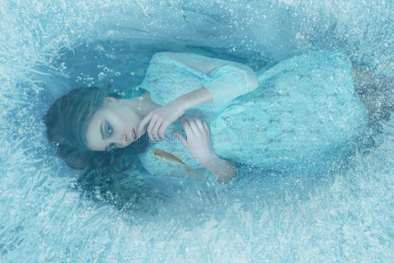 Ein Meerjungfraumädchen in einem blauen Weinlesekleid liegt an der Unterseite des Sees Es wird mit Eisrand, Fisch schwimmt um es  lizenzfreie stockbilder
