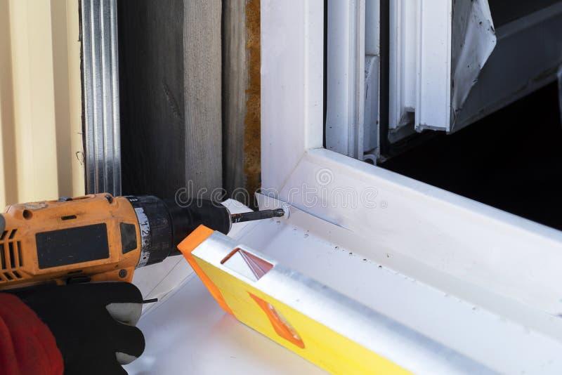 Ein Meister in den Handschuhen bohrt die Schrauben in einen Baum Installation des Fensterbretts auf der Straße mit einem Werkzeug lizenzfreies stockfoto