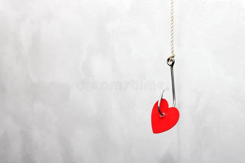 Ein Metallfischereihaken, der an einem Seil hängt, durchbohrte das rote Pappherz Konzept der Liebe stockfotos