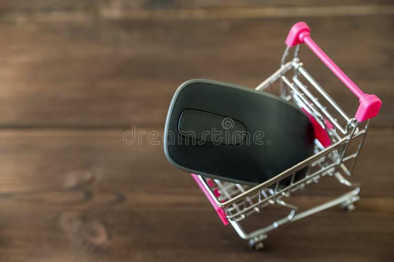 Ein Metallwarenkorb vom Supermarkt mit einer Computermaus Das Konzept von im Internet kaufen lizenzfreies stockbild