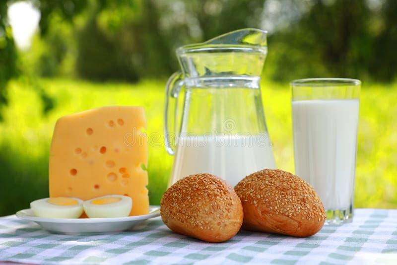 Ein Milchkrug, ein Glas Milch, ein Stück Käse und ein geschnittenes Ei auf einer Platte stockfotos