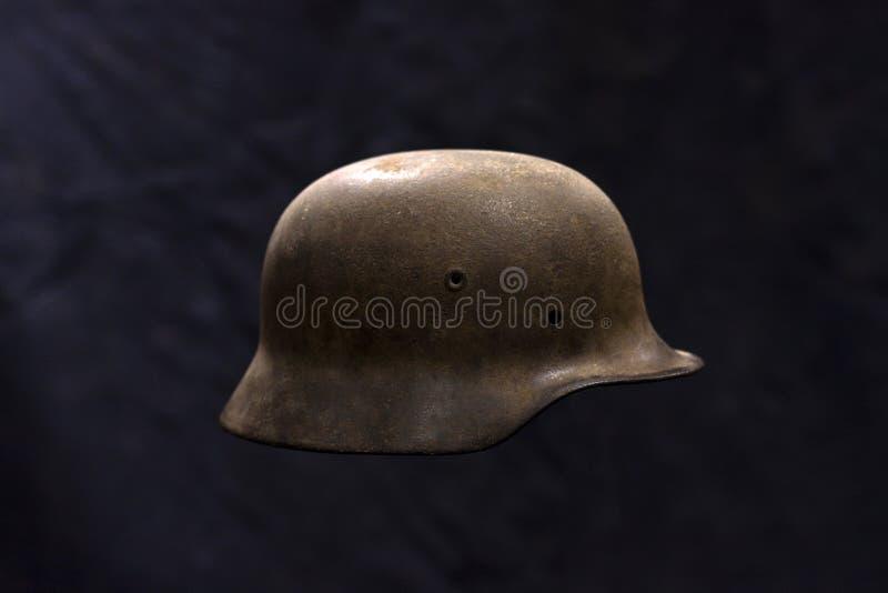 Ein Militärsturzhelm des rostigen deutschen Zweiten Weltkrieges auf dunklem Hintergrund stockfoto