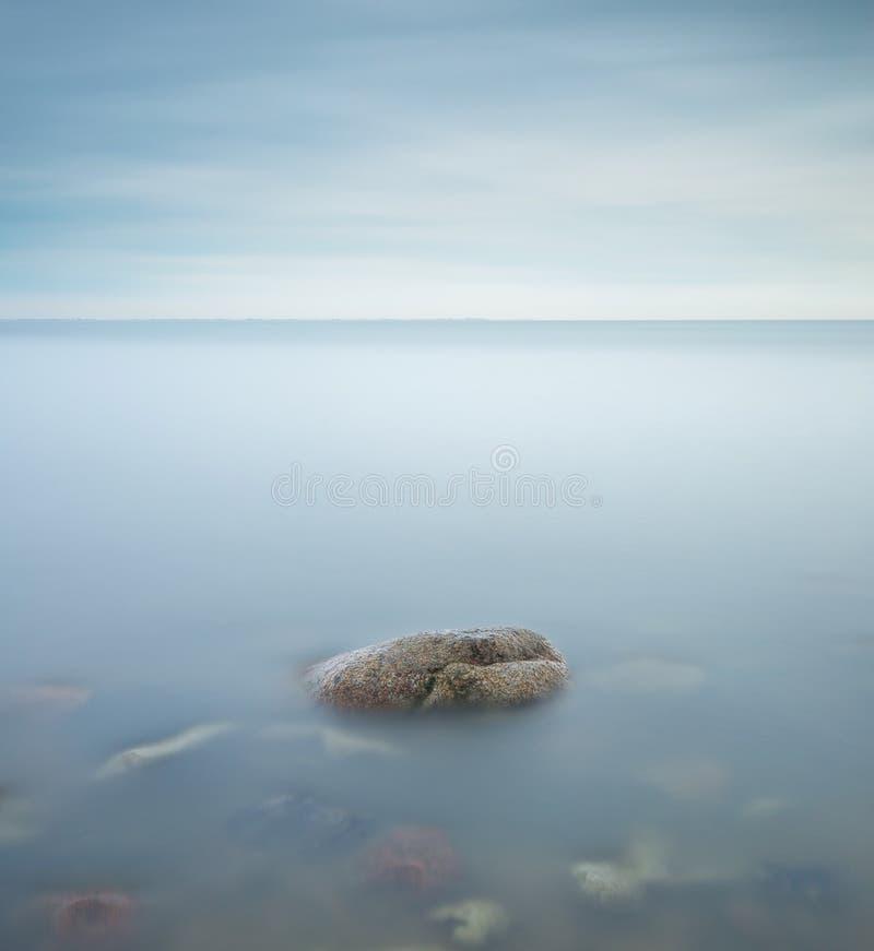 Ein Minimalismusfoto eines Felsens in einem See lizenzfreie stockfotos