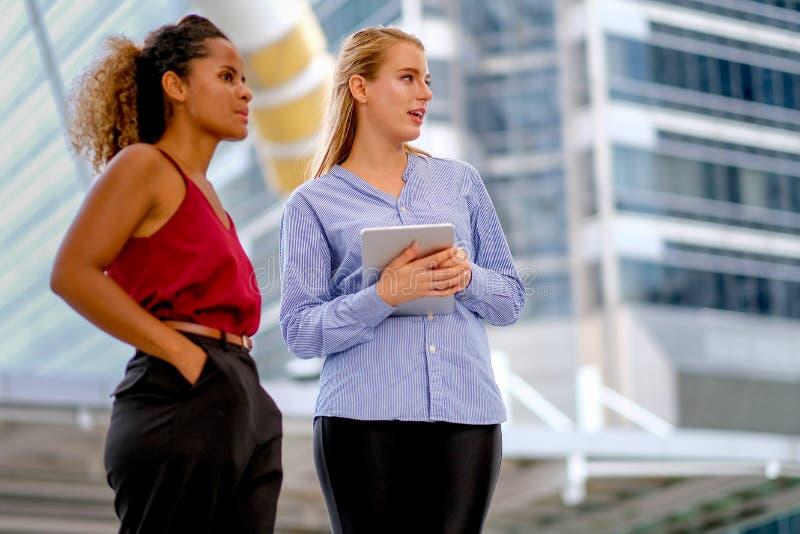 Ein Mischrassemädchenstand und mit weißem kaukasischem Mädchen sich besprechen, das Tablette hält lizenzfreies stockfoto