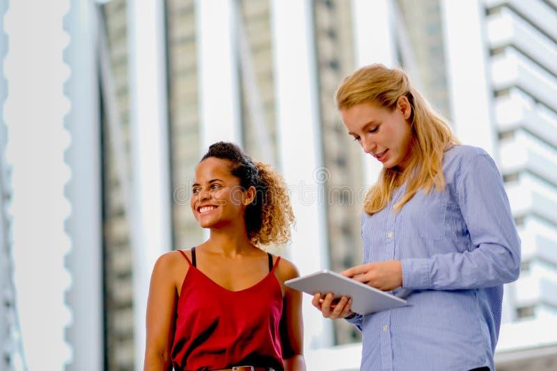 Ein Mischrassemädchenstand und mit weißem kaukasischem Mädchen sich besprechen, das Tablette hält lizenzfreie stockbilder