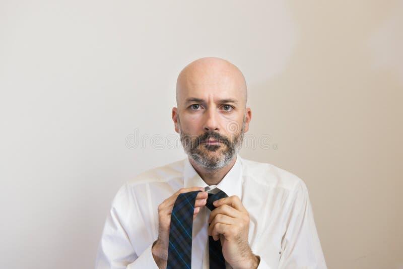 Ein mittlerer Altersmann mit Bart knotet seine Krawatte stockfotografie