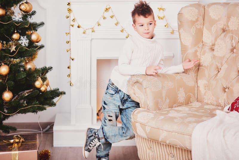 Ein Modekerl in einem Weiß strickte Strickjacke und Jeans und eine stilvolle Frisur hängt am Sofa Ein netter Junge steht nahe bei lizenzfreie stockfotos